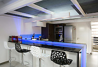 """Home Nemo"" is the name architect Alain Demarquette has given to this renovation of an apartment in the roof of a former telephone exchange. The kitchen is a knowing combination of materials, with a work surface and breakfast bar carved from a piece of polished black granite from Zimbabwe"