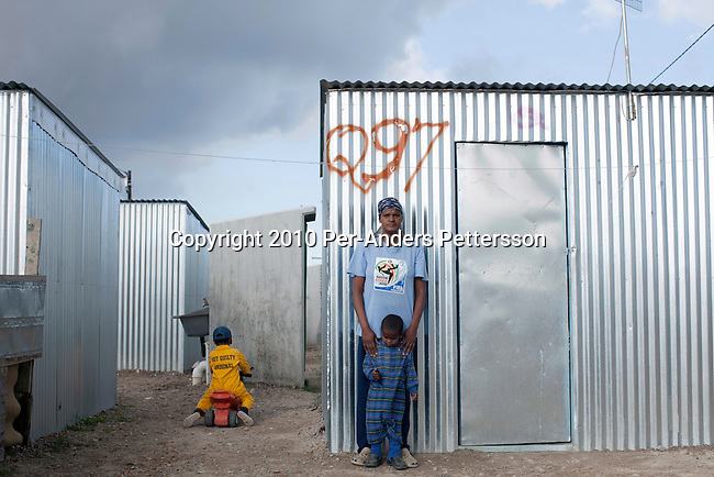 """CAPE TOWN, SOUTH AFRICA - MAY 3: Deborah Schericka, age 32, stands outside her tin shack with her son Frazier Sherick, age 10, on May 3, 2010, in Blikkiesdorp about 40 kilometers south of Cape Town, South Africa. Deborah used to live on the streets of Central Cape Town and she was recently forced to move away and dumped at this site. She had lived for years on the streets of Cape Town. The street people who refused to move here were put in prisons, such as Pollsmoor. Blikkiesdorp, which is Afrikaans for """"Tin Can Town"""", was given its name by its residents because of the row-upon-row of tin-like shacks made of corrugated iron. It was built by the City of Cape Town in 1997 and about 1600 one-roomed shacks were built. It has been known for its bad conditions and a dumping ground for shack dwellers from other areas around Cape Town. Recently many street people in Cape Town has been forcefully removed and relocated to this place. The ones that have refused has been put in holdings cells or prisons such as Pollsmoor Prison. This campaign has  identified in the preparation for the soccer World Cup, who starts on June 11, 2010 and goes on for a month. The City of Cape Town doesn't want international visitors to be hassled by street people. (Photo by Per-Anders Pettersson)"""