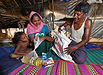 In their family's makeshift shelter in the Mainerghona Refugee Camp near Cox's Bazar, Bangladesh, Kamal Hasom and his wife Dildar Mamaz unpack food supplies they received from Caritas on October 27, 2017. Their 4-year old daughter Nuralam watches. <br /> <br /> They are among the more than 600,000 Rohingya who since August have fled violence in Myanmar for safety in Bangladesh.<br /> <br /> Hasom said they fled their village in Myanmar in late September after their house was burned by the Myanmar military.