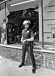 A LAPD officer in front of a looted record store on Crenshaw Blvd in South Central L.A.