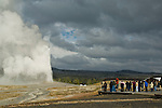 Crowd of tourists watching an eruption of geothermal steam and water venting out of Old Faithful Geyser, Upper Geyser Basin, Yellowstone National Park, Wyoming
