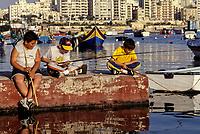 Spinola Bay, St. Julians, near Valletta, Malta.  Maltese Boys Fishing.