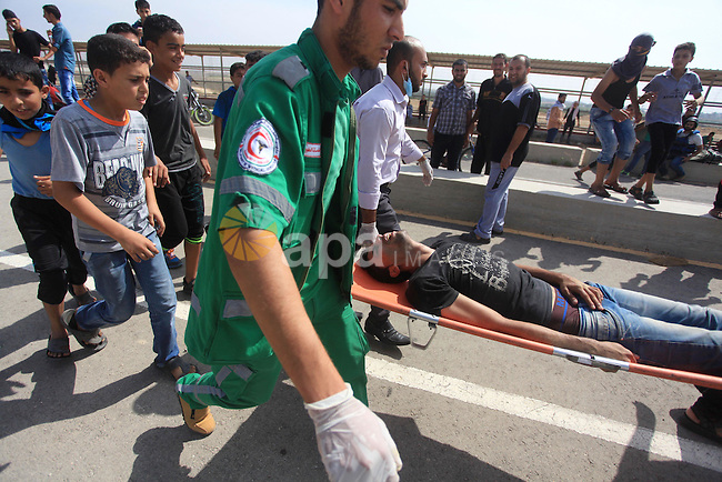 Palestinian medics carry an injured protesters during clashes with Israeli security forces next to the border fence with Israel, at the Erez crossing in the northern Gaza strip, on October 13, 2015. A wave of stabbings that hit Israel, Jerusalem and the West Bank this month along with violent protests in annexed east Jerusalem and the occupied West Bank, has led to warnings that a full-scale Palestinian uprising, or third intifada, could erupt. The unrest has also spread to the Gaza Strip, with clashes along the border in recent days leaving nine Palestinians dead from Israeli fire. Photo by Ashraf Amra