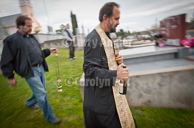 Father Blasko Paraklis pours wind on the grave of the honored departed as Miloje Milinkovic, Dan Sojoanovich and Father Budimir Andjelic watch on at St. Sava Church, Jackson