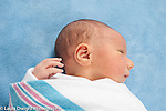 3 day old newborn baby boy closeup, looking to side elongated head shape from birth canal