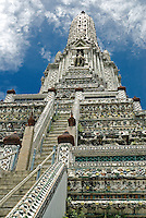 As you climb the steep staircases leading to platforms that circle the base of the 272 foot Wat Arun in Bangkok, you begin to see that the magnificent structure is adorned with ornate floral mosaics made with tiny pieces of porcelain originally brought to Bangkok as ballast in Chinese trading ships..