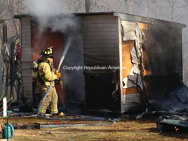 BETHLEHEM, CT - 15 Nov 2013 - 111513RH01 - A firefighter douses the inside of a burning shed outside a Guilds Hollow Road home in Bethlehem. Rick Harrison Republican-American