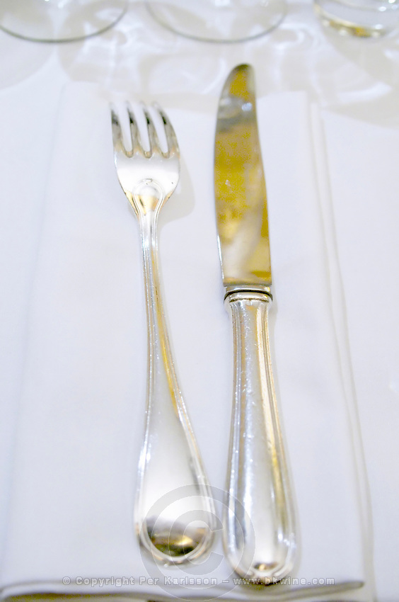 Knife and fork on a white linen napkin and table cloth in the restaurant Le Gourmandin in Beaune Cote d'Or Burgundy Bourgogne France Europe