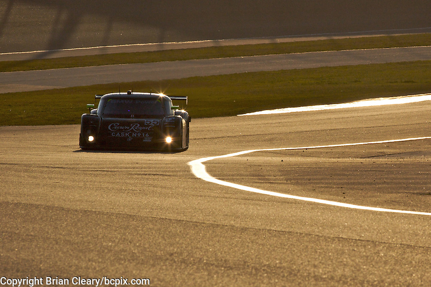 The #55 BMW Riley of Christophe Bouchut and Scott Tucker races through a turn at sunset during the Grand Prix of Miami, Homestead-Miami Speedway, Homestead, FL, March 2010.  (Photo by Brian Cleary/www.bcpix.com)