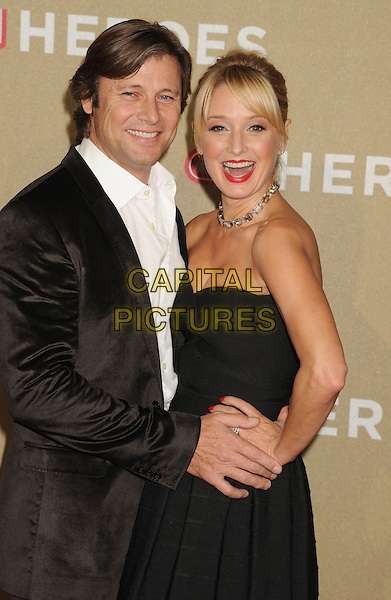 Grant Show, Katherine LaNasa.2012 CNN Heroes An All-Star Tribute held at the Shrine Auditorium, Los Angeles, California, USA..December 2nd, 2012.half  length black suit jacket white shirt strapless dress hand on hip married husband wife smiling mouth open side .CAP/ROT/TM.©Tony Michaels/Roth Stock/Capital Pictures