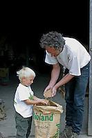 Bio-Bauernhof, Bauernhof, Bauer, Landwirt, Biobauer zeigt Kind Getreide