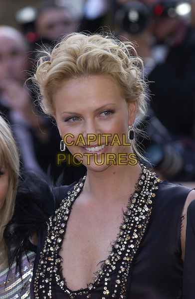 """CHARLIZE THERON.Arrivals at screening of """"The Life and Death of Peter Sellers"""".Cannes Film Festival, France 21st May 2004..portrait headshot black drop earrings low cut plunging neckline black dress with gold silver stones beading.sales@capitalpictures.com.www.capitalpictures.com.©Capital Pictures"""