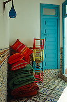 The brightly coloured rugs, cushions and small stools from the terrace are stacked up in the tiled hallway when not in use