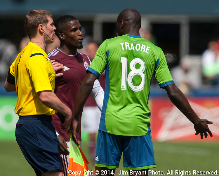 Referee Armando Villarreal separates Seattle' Djimi Traore (18) and Colorado Rapids Edson Buddle during an MLS match on April 26, 2014 in Seattle, Washington.  The Seattle Sounders beat the Colorado Rapids 4-1.  Jim Bryant Photo. ©2014. All Rights Reserved.