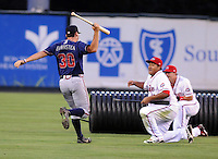 Members of the Rome Braves, including Cory Brownsten (30), left, and Greenville Drive, including Boss Moanaroa (29), front right, stage a mock battle, attacking from opposite sides of the field, during a lengthy rain delay before a game on July 5, 2012, at Fluor Field at the West End in Greenville, South Carolina. (Tom Priddy/Four Seam Images)