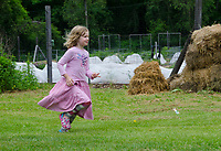 Young girl runs in the the garden, YCG, Maine, USA