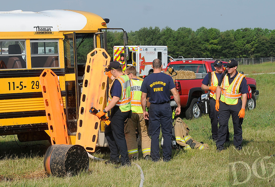 STAFF PHOTO FLIP PUTTHOFF<br /> A school bus was used to simulate the cabin of a corporate aircraft during the drill on Tuesday Sept. 9 2014 at the Rogers airport.
