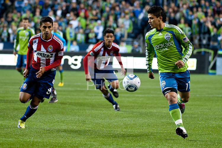 Fredi Montero (11) of the Seattle Sounders works the ball against Chivas USA defender Mariano Trujillo (8) at the XBox 360 Pitch at Quest Field in Seattle, WA on October 15, 2010. The Sounders defeated Chivas USA 2-1.