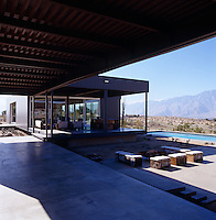 View from under a large covered terrace over an exterior seating area and the swimming pool to the distant mountains