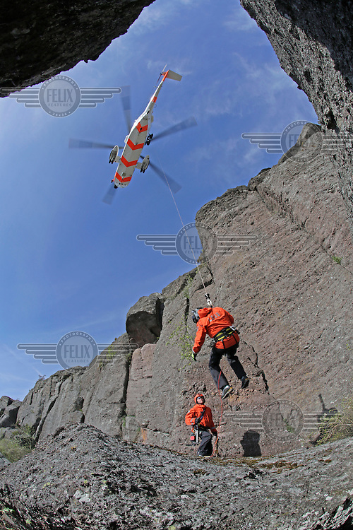 Practicing rescue from a ledge on a rock face using a rescue hoist.   Crew from Norwegian Air Force 330 squadron, flying Westland Sea King helicopter. The core mission of the squadron is SAR (search and rescue), but they also fly HEMS (Helicopter Emergency Medical Service), complementing the civilian air ambulance service.<br /> This crew fly out of Rygge Air Station, Norway.