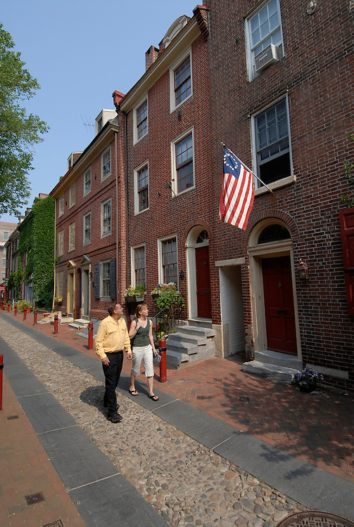 Elfreth's Alley, couple viewing houses, mod rel..Philadelphia, Pennsylvania, PA USA.  Photo copyright Lee Foster, 510-549-2202, lee@fostertravel.com, www.fostertravel.com. Photo 278-30458