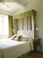 This elegant guest bedroom has a matching bed canopy and curtains