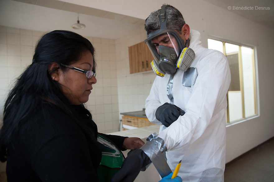 "Donovan's assistant helps Donovan get ready to begin the cleanup of an unsolved homicide in Cuernavaca, Morelos – one of Mexico's most dangerous cities on August 7, 2015. The 66-year-old victim was a retired economics lecturer from the local university, and was killed in January of this year. The cleanup took place eight months later. The victim's family has since moved away to avoid further trouble. They remarked that justice is slow in Mexico and expressed dissatisfaction with the police investigation, but appreciated Donovan's discretion and professionalism. Donovan Tavera, 43, is the director of ""Limpieza Forense México"", the country's first and so far the only government-accredited forensic cleaning company. Since 2000, Tavera, a self-taught forensic technician, and his family have offered services to clean up homicides, unattended death, suicides, the homes of compulsive hoarders and houses destroyed by fire or flooding. Despite rising violence that has left 70,000 people dead and 23,000 disappeared since 2006, Mexico has only one certified forensic cleaner. As a consequence, the biological hazards associated with crime scenes are going unchecked all around the country. Photo by Bénédicte Desrus"