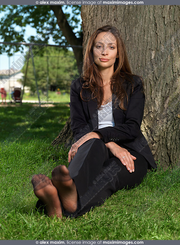 Young attractive businesswoman sitting barefoot on green grass in a park