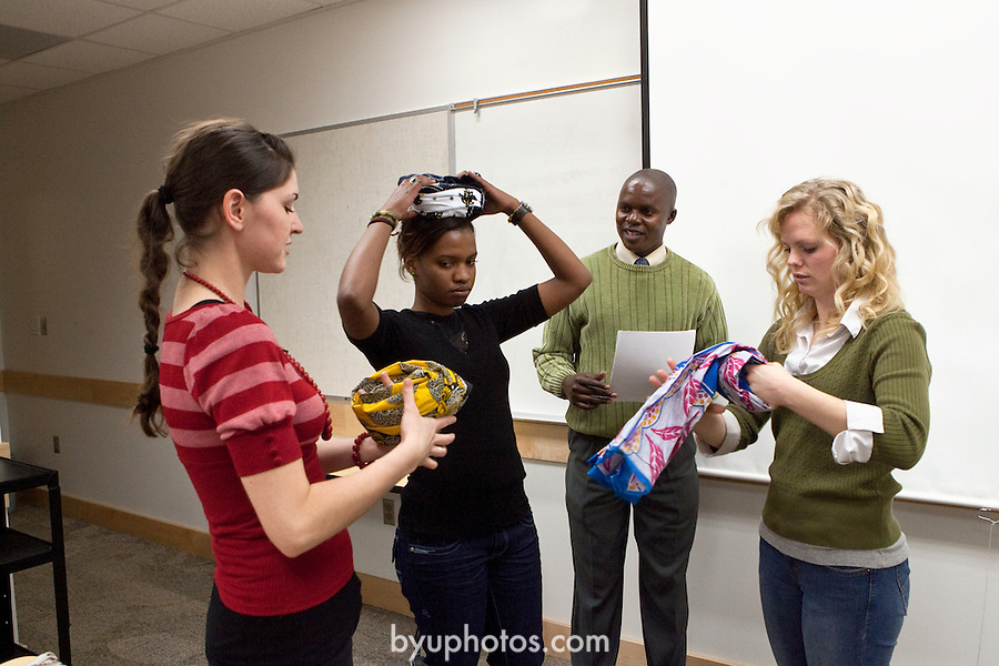 0712-12 358.CR2.Amram Musungu teaching a Swahili language and cultural class.Isaabella Dias showing Mary Jackson (yellow Kanga) and Briana Christensen (blue Kanga)  how to use a Kanga (or Khanga)..December 10,  2007..Photography by Mark  A. Philbrick..Copyright BYU Photo 2007.All Rights Reserved .photo@byu.edu  (801)422-7322