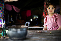 Nit Jombadin siting by a table in her simple house. Her child is one of thousands of innocent victims of indiscriminent bombings and killings in southern Thailand. Thailand is struggling to keep up appearances as the land of smiles has to face up to its troubled south. Since 2004 more than 3500 people have been killed and 4000 wounded in a war we never hear about. In the early hours of January 4th 2004 more than 50 armed men stormed a army weapons depot in Narathiwat taking assault rifles, machine guns, rocket launchers, pistols, rocket-propelled grenades and other ammunition. Arsonists simultaneously attacked 20 schools and three police posts elsewhere in Narathiwat. The raid marked the start of the deadliest period of armed conflict in the century-long insurgency. Despite some 30,000 Thai troops being deployed in the region, the shootings, grenade attacks and car bombings happen almost daily, with 90 per cent of those killed being civilians. 21.09.07. Photo: Christopher Olssøn.