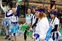 Cheerleaders facetiously cheering fictitious bottle water company. MayDay Parade and Festival. Minneapolis Minnesota USA