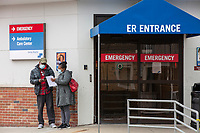 A couple wearing face-masks are seen outside the Emergency Department entrance at Carney Hospital in Dorchester, Massachusetts, on Mon., March 23, 2020. Earlier this week, it was announced that Carney Hospital would be the United States first dedicated patient ward for Coronavirus (COVID-19) treatment.