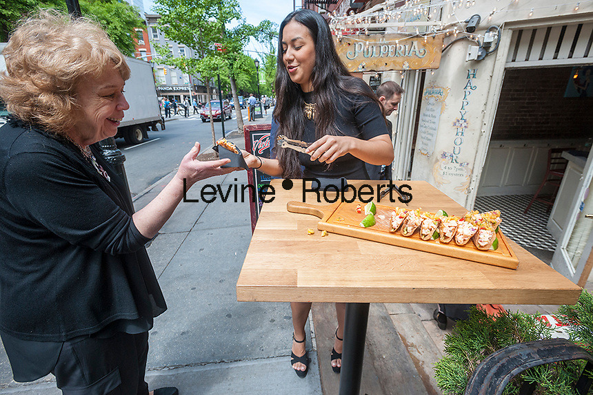 A hostess from La Pulperia serves seafood tacos after the unveiling of the new wayfinding kiosks that stand at either end of Restaurant Row in New York, West 46th street between 8th and 9th Avenues, on Tuesday May 16, 2017. At least four years in the making the illuminated kiosks show the names of the many eateries that populate the street. The unveiling is just in time for the Taste of Times Square event taking place on the street on June 5. (© Richard B. Levine)