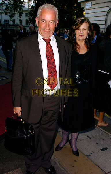 """SIMON CALLOW & GUEST.""""Volver"""" UK film premiere, Curzon Mayfair, London, UK..August 3rd, 2006.Ref: CAN.full length grey gray suit briefcase black dress.www.capitalpictures.com.sales@capitalpictures.com.©Can Nguyen/Capital Pictures"""