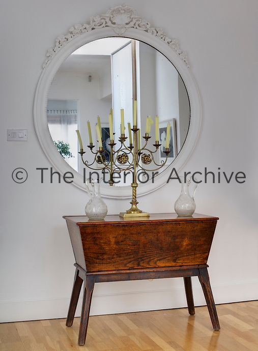 The floral carvings on an old white-painted mirror are echoed in the curlicues of a gilt candelabra displayed on an antique table