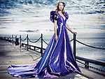 Young woman wearing a beautiful long blue evening gown standing at waterfront, artistic fashion portrait