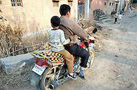 China. Province of Henan. Village Nan Laoguanzui. A man and a boy ride a motorbike. The boy was kidnapped in the village of Shifeng in Shaanxi province on may 12 2002, sold to a family in the village of Nan Laoguanzui. The police found him and brought him back to his family on march 4 2004. The family has then decided, because of the poverty they live in, to resell his child to the family which already bought him (from the thieves) and with whom he lived happy for almost two years. The man on the motorcycle is his new father. © 2004 Didier Ruef
