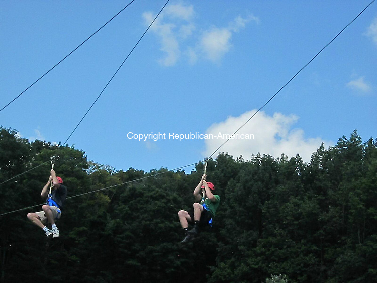 WOODBURY, CT - 2 Aug 2012 - Burlington residents Steve Porat, left, and his son Brendan Porat, right, hang in harnesses from the new zip line at Woodbury Ski Area in Woodbury. Rick Harrison Republican-American