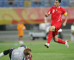 10 August 2008: Zheng Zhi (CHN) (8) leaps over goalkeeper Logna Bailly (BEL) (1).  The men's Olympic soccer team of Belgium defeated the men's Olympic soccer team of China 2-0 at Shenyang Olympic Sports Center Wulihe Stadium in Shenyang, China in a Group C round-robin match in the Men's Olympic Football competition.