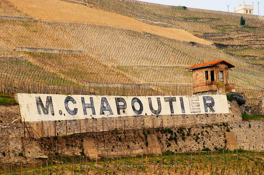 Painted black on white on stone walls M Chapoutier. The Hermitage vineyards on the hill behind the city Tain-l'Hermitage, on the steep sloping hill, stone terraced. Sometimes spelled Ermitage. Chante Alouette and le Meal vineyards. Tain l'Hermitage, Drome, Drôme, France, Europe