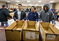 NWA Democrat-Gazette/BEN GOFF @NWABENGOFF<br /> Yair Benitez (from left), Issac Arce and Jesus Avila fill boxes to be delivered while volunteering with their teammates from the Rogers Heritage soccer team Thursday, Nov. 28, 2019, during the annual Thanksgiving meal distribution at the First Baptist Church Olive Street campus in Rogers. <br /> <br /> Paul Olinger, a church member who helped coordinate the meal, said the event started 20 years ago 'As an outreach of the church to show the love of Christ in the community'. Volunteers from the church and the community cooked, packaged and delivered boxed meals that included ham, green beans, mashed potatoes and deserts. <br /> <br /> Open to anyone, a line wrapped around the room as families picked up boxes of food to take home, but Olinger estimates that 98 percent of the meals are delivered by volunteers.