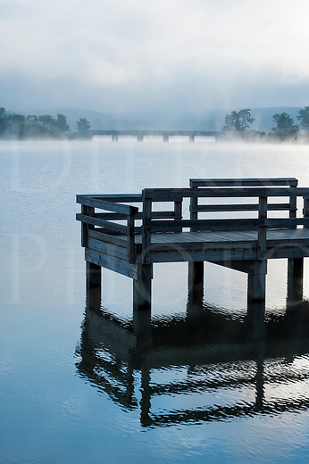 Foggy lake in early morning light with fishing dock in foreground.