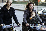 AMSTERDAM - NETHERLANDS - 19 OCTOBER 2004 -- Bicycles are famously the most popular mean of transportation in the city. A mother with child on a bicycle with a friend, while the baby is drinking out of the baby -bottle during the ride.-- PHOTO:  EUP-IMAGES / JUHA ROININEN