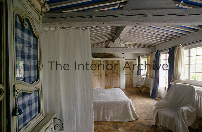 This simply furnished bedroom has a brick floor and exposed rafters