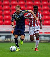 4th July 2020; Bet365 Stadium, Stoke, Staffordshire, England; English Championship Football, Stoke City versus Barnsley; Cauley Woodrow of Barnsley and Bruno Martins Indi of Stoke City chase a loose ball