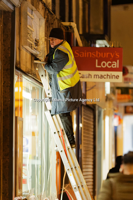 Pictured: A worker assesses the damage outside Sainsbury's in Uplands, Swansea, Wales, UK.  Tuesday 13 February 2018<br /> Re: A Sainsbury's shop sign at the Uplands local store in the Uplands area of Swansea has collapsed onto the pavement hitting a woman in south Wales, UK.