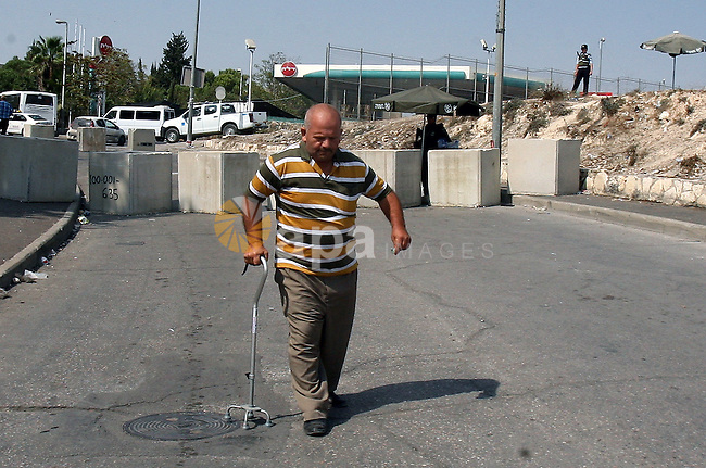 A Palestinian man walks between cement blocks at a newly erected checkpoint in Jerusalem's neighborhood of Issawia on October 19, 2015. Israeli police began erecting a wall in east Jerusalem to protect a Jewish neighbourhood subject to firebomb and stone attacks launched from an adjacent Palestinian village. Photo by Mahfouz Abu Turk