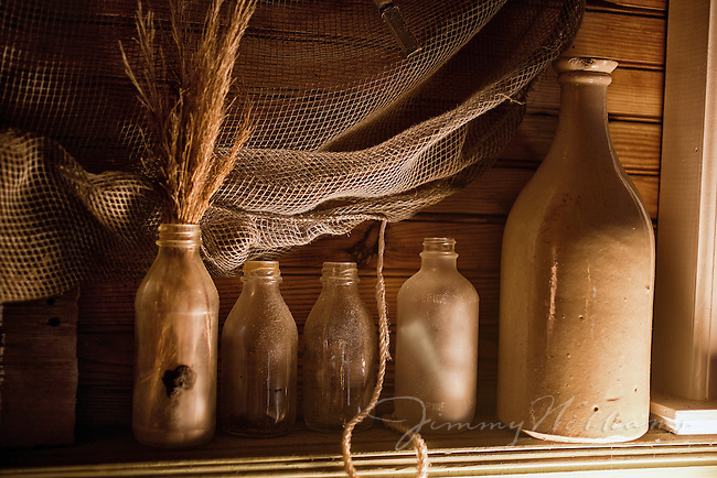 Old milk bottles and old fish net create a display piece in an old beach cottage