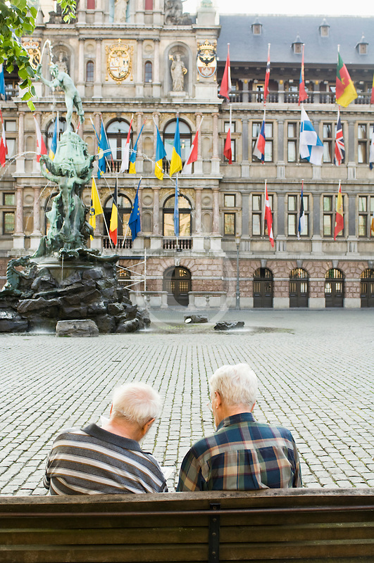 Belgium, Antwerp, Two men on bench in Grote Markt in front of Town Hall, Stadhuis, and Brabo statue