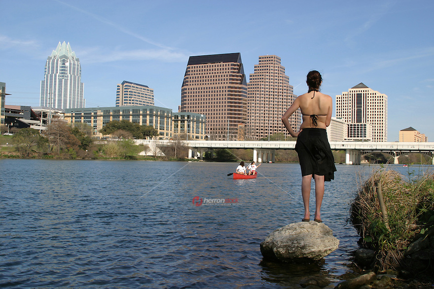 Woman looks on as the canoes navigate Lady Bird Lake Austin; TX